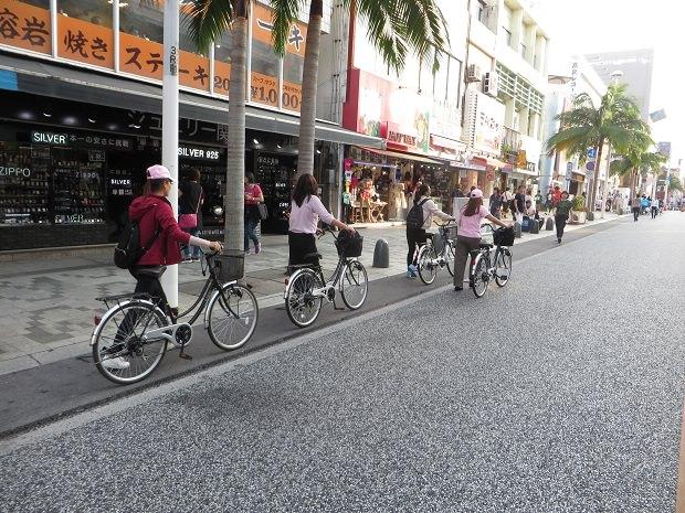 自転車を押して通る観光客
